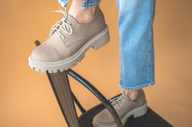 Women legs in stylish casual shoes, modern sneakers with white laces close-up. fashionable teen girl clothes style photo