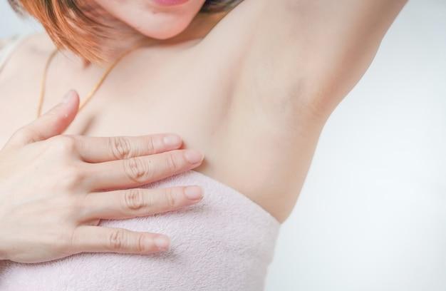 女性は滑らかな脇の下ケア製品を使用して、腕を持ち上げて美しい脇の下の肌を見せます