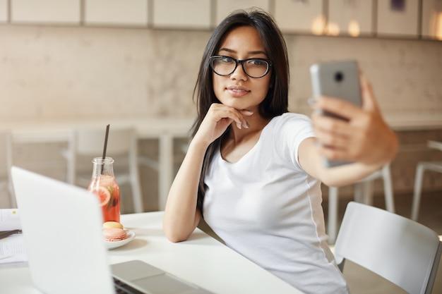 女性は自分が好きです。携帯電話を使ってカフェで自分撮りをしている若いアジア人学生。