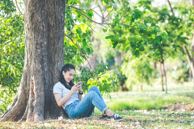 Women listen to music and relax under the trees.