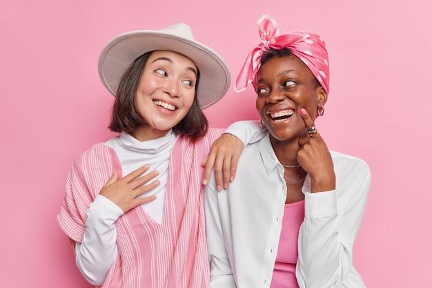 女性は陽気な表情でお互いを見て、ピンクで隔離されたファッショナブルな服に広く身を包んだ面白い笑顔について話し合う