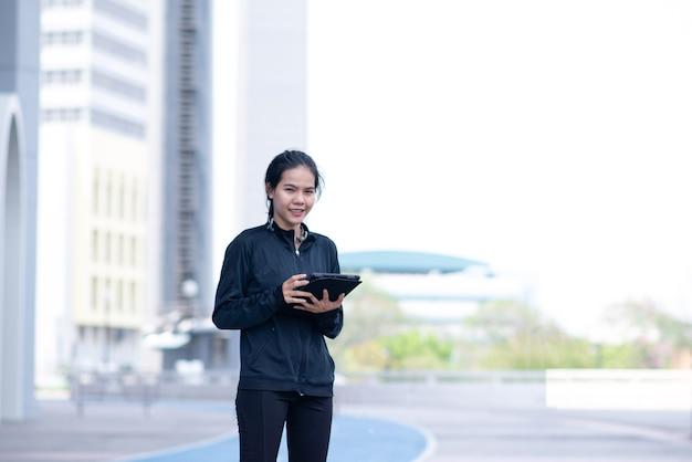 여성은 검은 색 운동복을 들고 태블릿을 만지면 미소 짓고 행복해 보입니다.