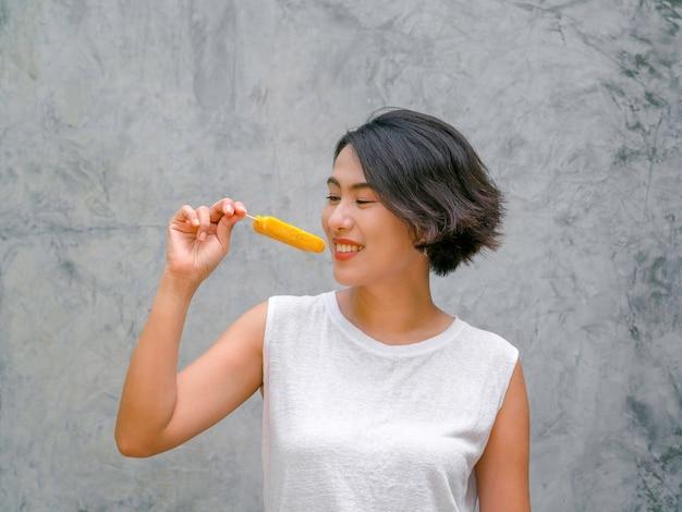 アイスキャンデーを見ている女性。夏のコンクリートの壁の背景に黄色のアイスキャンデーを食べるカジュアルな白いノースリーブシャツの幸せなアジアの女性の短い髪。