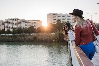 ブリッジから川を見ている女性