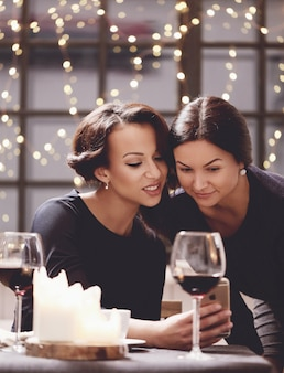 Женщины смотрят на смартфон в ресторане
