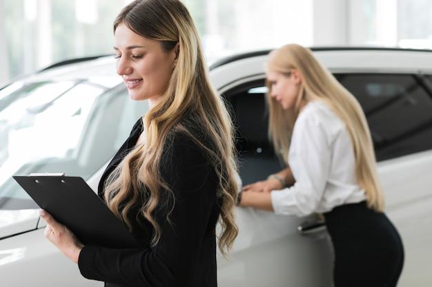 Donne che osservano via nello showroom di automobili