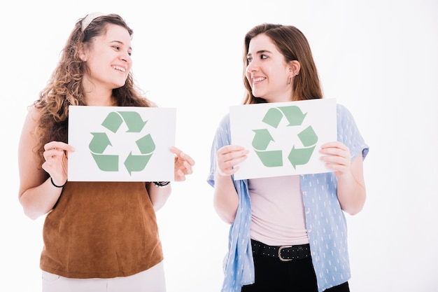Women looking at each other holding recycle icon placard on white backdrop