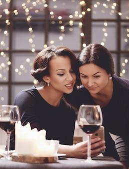 Women looking at smartphone in restaurant