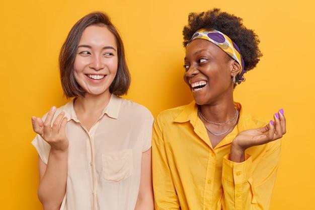 여성들은 세련된 옷을 입은 서로를 기쁘게 바라보며 활짝 웃고 노란색 스튜디오에 격리된 어깨를 나란히 하고 손을 들고 있습니다