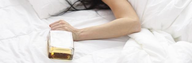 ウイスキーのボトルを手に白いベッドに横たわっている女性。アルコール依存症の概念