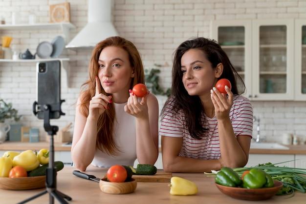 음식을 준비하면서 브이로그를 만드는 여성들