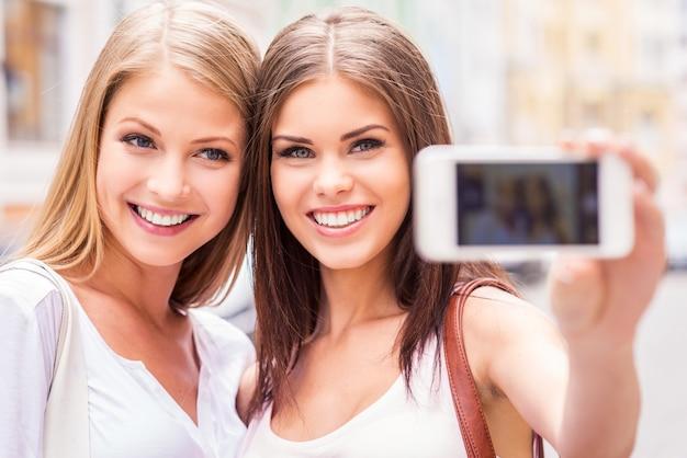 셀카를 만드는 여성들. 야외에 서서 셀카를 찍고 웃고 있는 두 명의 매력적인 젊은 여성