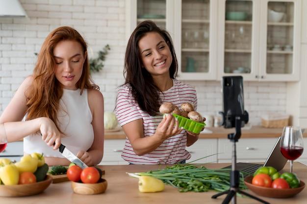 Donne che fanno un vlog mentre preparano il cibo