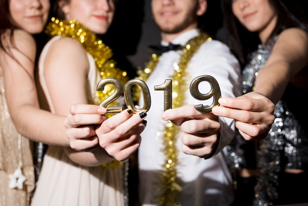 Women and man in evening wear with 2019 numbers