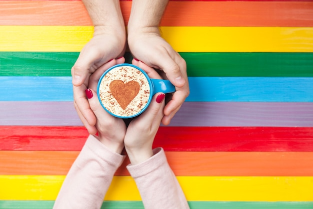 Women and man holding cup of coffee with heart shape symbol on color surface