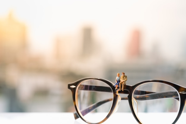 A women and a man in love sitting on glasses with city backgrounds.