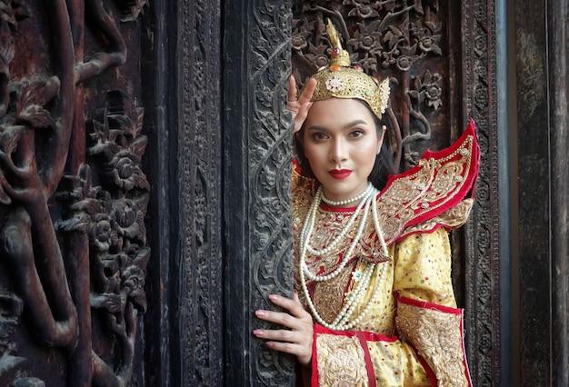 Women in mandalay traditional costume standing by wooden door