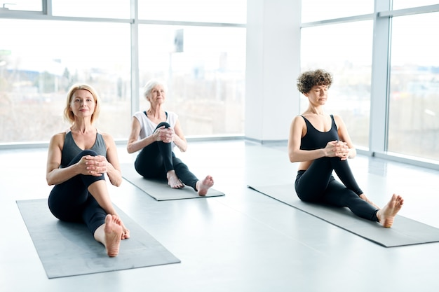 Women on mats doing yoga next to a large window