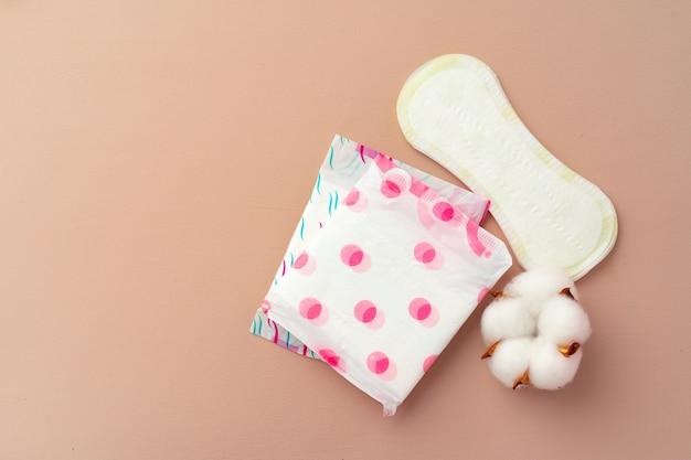 Женские медицинские прокладки и цветок хлопка на бумажном фоне