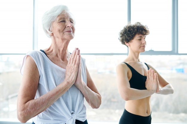 Women meditating and doing yoga next to a large window