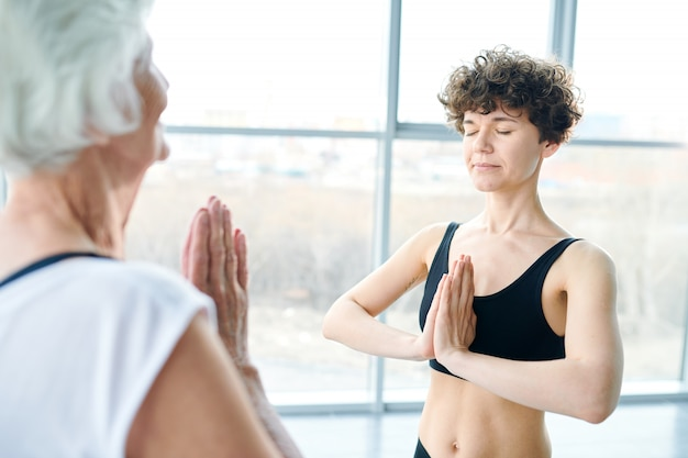 Women meditating and practicing yoga next to a large window