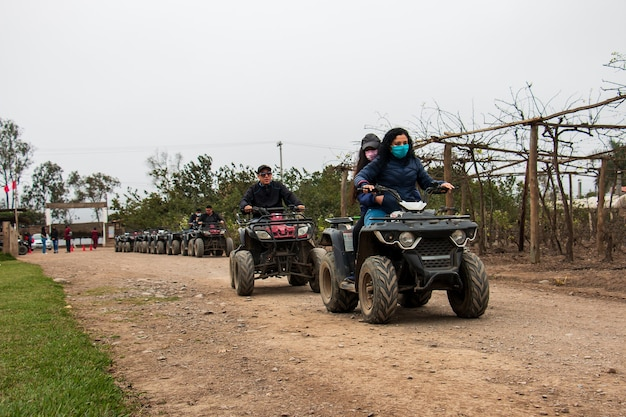 Women and men on atvs are enjoying a ride in a field