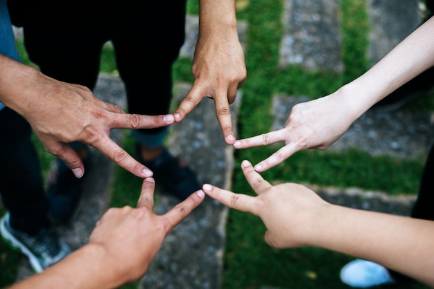 Women and men friends make star shape from fingers. success, friendship concept.