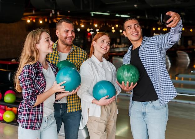 Donne e uomini che tengono palle da bowling colorate