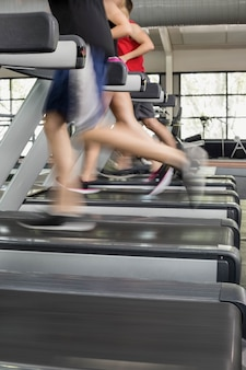 Women and men running on a treadmill at the gym