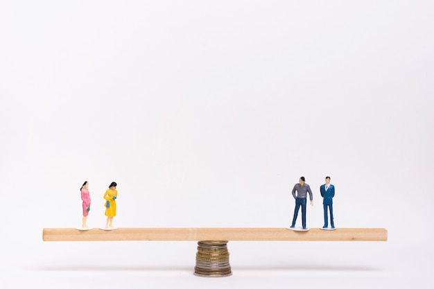 Women and men standing in balance on seesaw