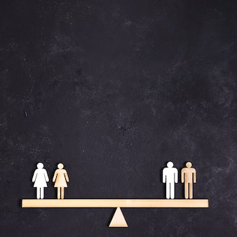 Women and men standing on seesaw copy space