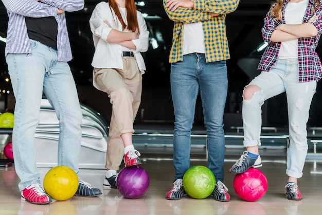 Women and men with balls in a bowling club