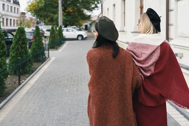 도시의 도시 배경 위에 우아한 가을 옷과 안경 여성 모델