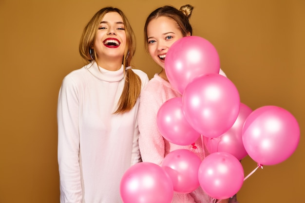 Women models with pink air balloons on golden wall