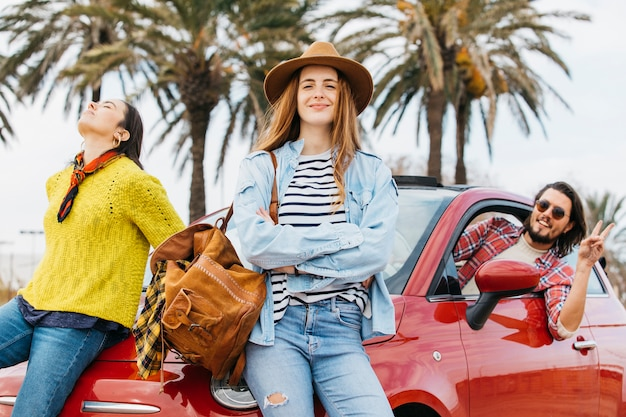 Women near man leaning out from car and showing peace gesture