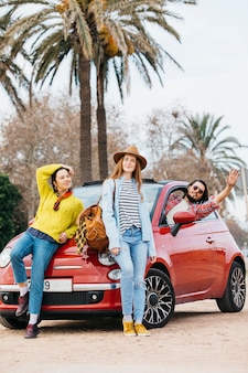 Women near man with upped hand leaning out from car