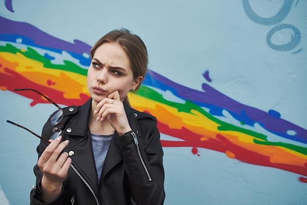 虹の形をした壁の落書きの近くの女性