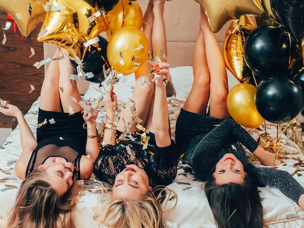 여성의 밤. 파티 여가 시간. 침대 다리에 누워있는 여성. 청소년의 기쁨과 자유. 반짝이 색종이와 풍선.