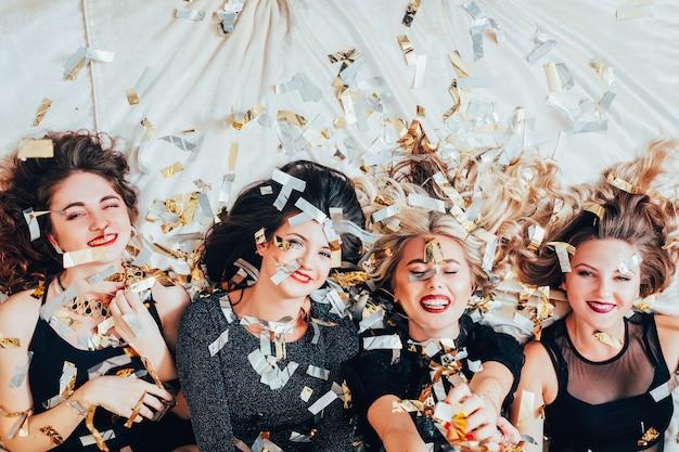여성의 밤. 파티 여가 시간. 편안한 침대에 누워 웃는 여성. 청소년의 기쁨과 자유. 주위에 반짝이 색종이.