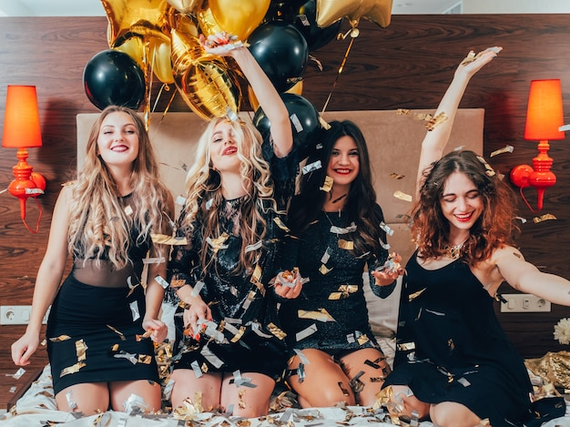 여성의 밤. 파티 여가 시간. 침대 포즈에 웃는 여성. 청소년의 기쁨과 자유. 반짝이 색종이와 풍선.