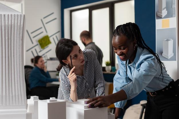デスクオフィスに立っている建築家の職業の女性