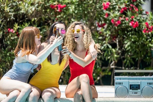 Женщины разных национальностей в купальниках веселятся в бассейне. концепция гей-прайда
