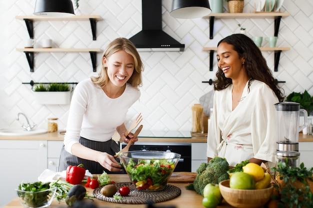 さまざまな国籍の女性が幸せで、キッチンでサラダを調理しています