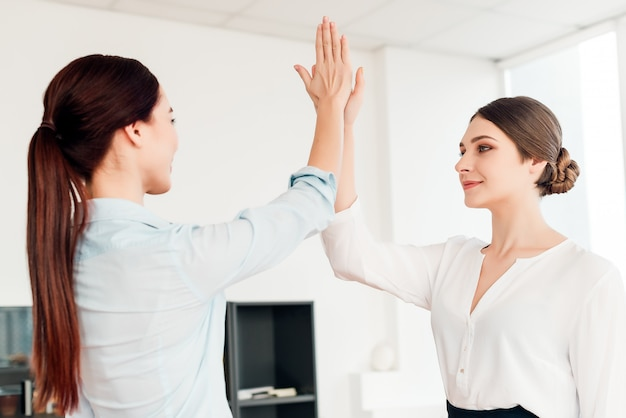 Women in the office co working and giving high five to each other
