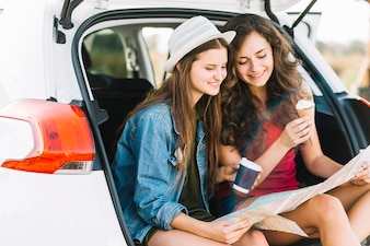 Women on car trunk with map
