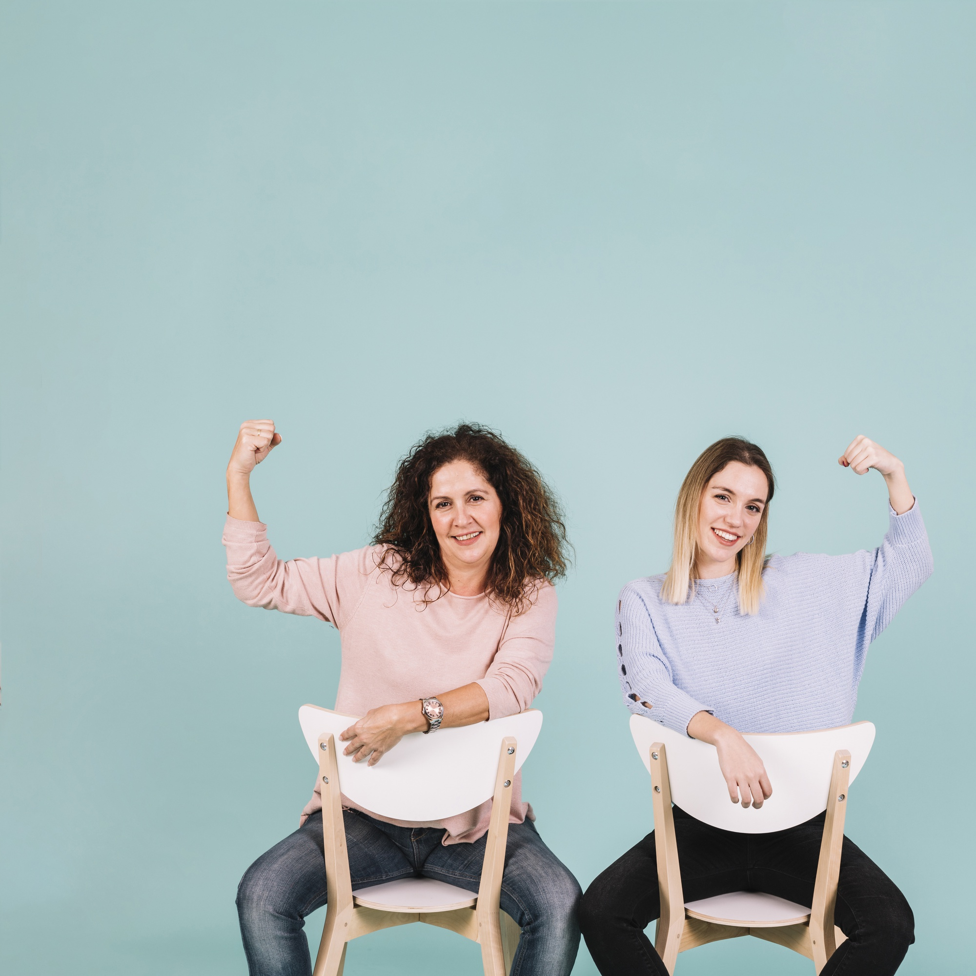 Women on chairs showing power gesture