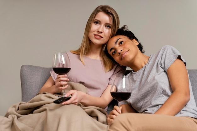 テレビを見たり、ワインを飲んだりするソファの上の女性