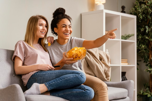 Женщины на диване смотрят телевизор и едят чипсы