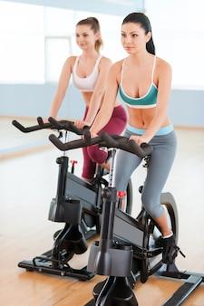 エアロバイクの女性。ジムの自転車で運動するスポーツウェアの2人の美しい若い女性