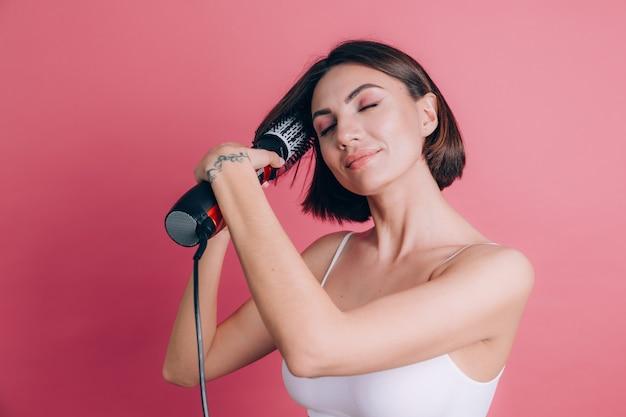 ピンクの背景の女性は髪をスタイリングするために丸いブラシヘアドライヤーを保持します